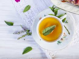 mint leaves and tea in the cup on a white wooden table