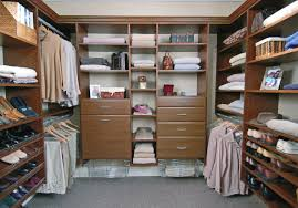 endearing modern walk in closet features brown wooden storage drawers and single hanging bars