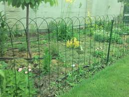 garden edging fence. Green Garden Fences With Several Dark Support Posts Separate Plants And Flowers From Lawns. Edging Fence