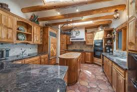 clear varnished wooden cabinets and diamond patterned refrigerator wood panel with solid wood kitchen island with