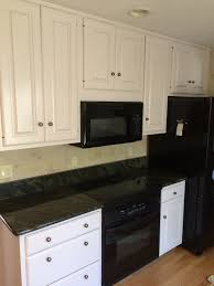 refinishing old wall mounted oak kitchen cabinets painting with white color and mounted microwave under wooden cabinet plus black granite countertop and