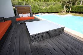 sophisticated white porcelain stone coffee table on dark wooden deck around pool as patio furnishing ideas