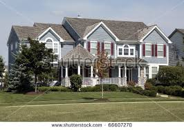 cedar roof. large home with red shutters and cedar roof