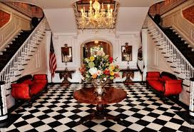 black and white ceramic floor tile patterns for luxury home decoration with beautiful flower arrangement above large round table between two stairs