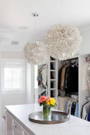 gorgeous white walk in closet features two pottery barn capiz lotus flower chandeliers hung above a long and narrow white island topped with honed white