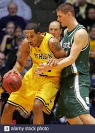 University of Michigan's center Courtney Sims (L) drives against Michigan  State's center Paul Davis during the