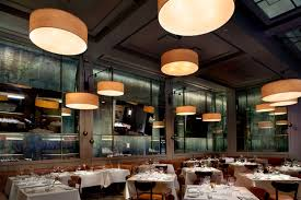 designed by icrave abe arthur s offers a main dining room decorated with aged mirrors large overhead light fixtures
