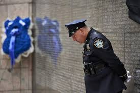 manhattan ceremony honors memory of fallen nypd officers ny  an nypd officer pauses in quiet reflection at the battery park city memorial on thursday