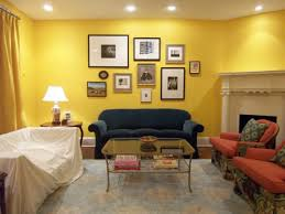 living room yellow wall paint blue sofa simple glass table vintage carpet wooden end table