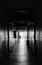 Black and white view looking down long empty hallway.