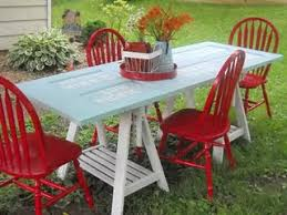 a unique outdoor painted old door table with ikea saw horses and painted red chairs
