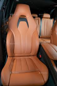 red perforated leather car seat with the unfocused car interior in the background stock photo