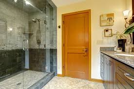 steam shower is enclosed by floor to ceiling tempered glass wall and door