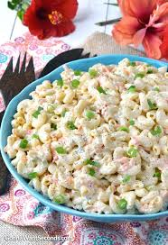 authentic hawaiian macaroni salad in a blue bowl with wooden serving fork and gumamela on the