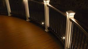 curved trex transcend railing is illuminated by led pyramid post cap lights and the perimeter of