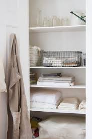 decluttered linen closet with fabric bags storage crates and folded bed sheets and bath