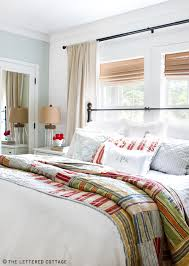 Bed in front of window. Curtains hanging on either side of bed ... & Beautiful master bedroom over at The Lettered Cottage. So much to love, but  my favorite is the quilt - great punch of color Adamdwight.com