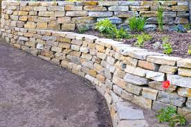 stone retaining walls running beside a packed dirt road meadow stone retaining wall blocks backyard retaining