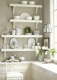 kitchen four white wooden wall mounted shelves on grey wall over white wooden cabinet