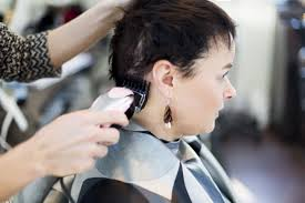 a woman having her head shaved by a hairdresser