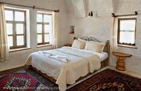 rug for bedroom. two hand made rugs are ideal for this bedroom which has stone walls. whenever you have natural walls - such as wood, or brick placing on the rug e