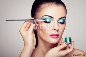 makeup artist applies eye shadow beautiful woman face perfect makeup makeup detail