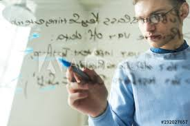 low angle portrait of young it professional wearing glasses writing formulas on glass wall and planning