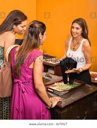s clerk showing necklace to women shoppers in boutique stock s clerk showing necklace to women shoppers in boutique
