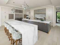 calacatta marble kitchen waterfall: a large contemporary kitchen features a calcutta marble waterfall kitchen island seating five white and gray
