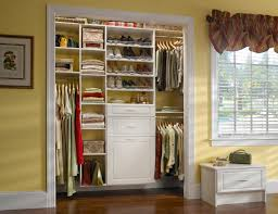 reach in closet in white raised panel with shoe shelves hamper and bench in room
