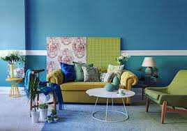 the walls in this room are painted a soulful teal blue that is repeated in the flooring by way of an ombre effect carpet that cozies up this living space