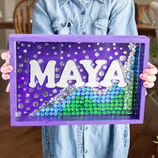 child holding a personalized mermaid wall art sign in purple green blue and silver