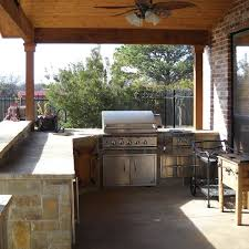 designed with natural stone to complement the natural wood ceiling this outdoor kitchen design was