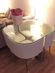 stylish space saving glass table with four comfortable cream chairs