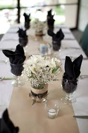 Kraft paper table runners, black napkins, white flowers in mason jars with  burlap and