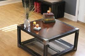 wood metal coffee table frame with top and candles vase books above glossy wooden floor ottonom shoes below mirrored glass rustic industrial square wheels