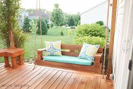 a wooden porch swing on a deck