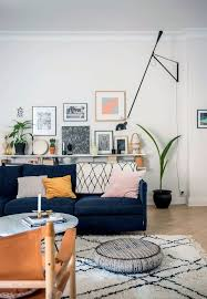 Amazing wall art gallery, full of color. Dark blue couch, perfectly  patterned rug
