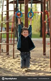 happy smiling boy hanging on gymnastic rings on the outdoor playground candid portrait stock