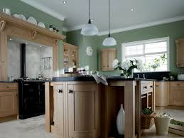 maple kitchen cabinet with green wall paint color also black countertop