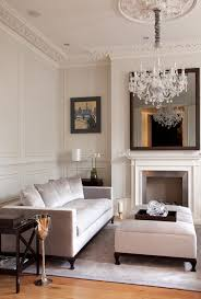 living room with bed: living room with a mirror over fireplace and crystal chandelier above an ottoman