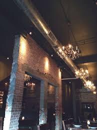exposed ceiling lighting basement industrial black. distressed brick tall ceilings exposed duct work hanging chandeliers ceiling lighting basement industrial black a