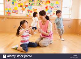 Nursery Teacher Nursery Teacher And Children Playing At Day Care Center Stock Photo