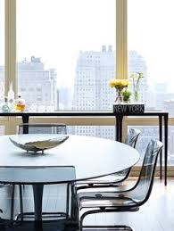 moderns dining room features an oval marble top dining table saarinen oval dining table lined with black acrylic dining chairs ikea tobias chairs