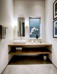 minimalist Japanese bathroom with white concrete walls and light woods