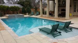 traditional swimming pool with tanning ledge and raised spa