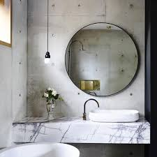 Set against an industrial backdrop, a round mirror softens the aesthetic of  this minimal bathroom