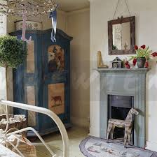 antique decoratively painted cupboard in corner of small bedroom with rustic wooden horse in blue grey fireplace
