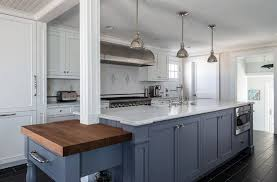 Beautiful kitchen with white cabinets white marble countertop and dark blue  island