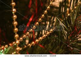 gold beads on a green christmas tree with red strands of tinsel i63
